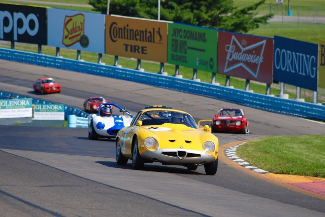 Joe Colasacco (#8), driving his 1963 Alfa Romeo TZ-1, leads Henry Gentry (#4) in a 1964 Ginetta G4 up through the esses.